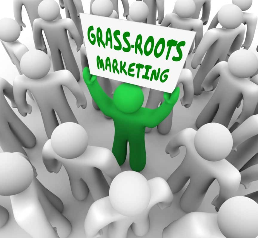 """A green figure standing in a crowd of others holding a sign that says """"Grass Roots Marketing"""""""